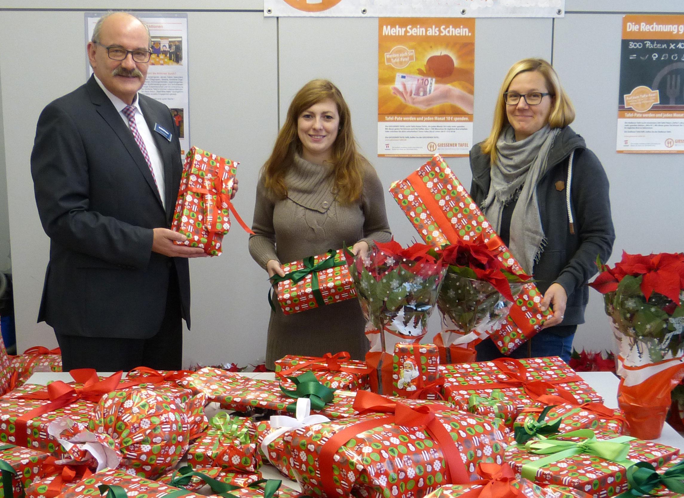 Karstadt-Geschäftsführer Lothar Schmidt (l.) und Michaela Thurner (r.) übergeben 160 Geschenke an Anna Conrad (M.)