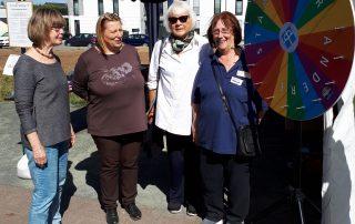 Mitarbeiterinnen der Tafel-Ausgabestelle in Linden vor dem Glücksrad